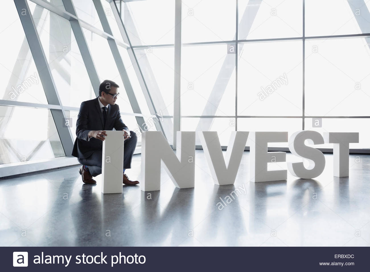 Man in suit l'organisation 'Investir' lettres Photo Stock