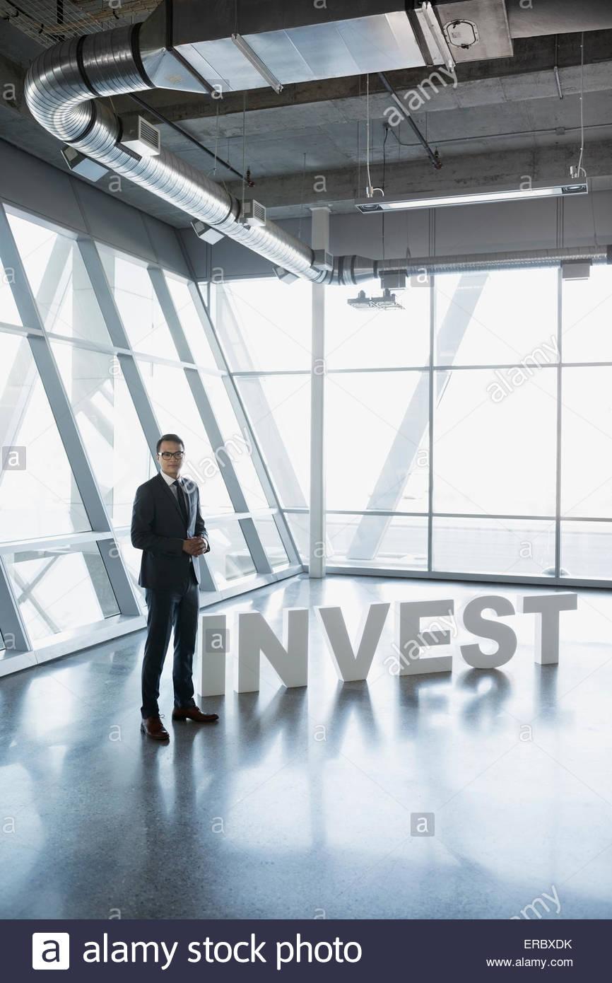 Portrait d'affaires en litige à côté de 'Investir' lettres Photo Stock
