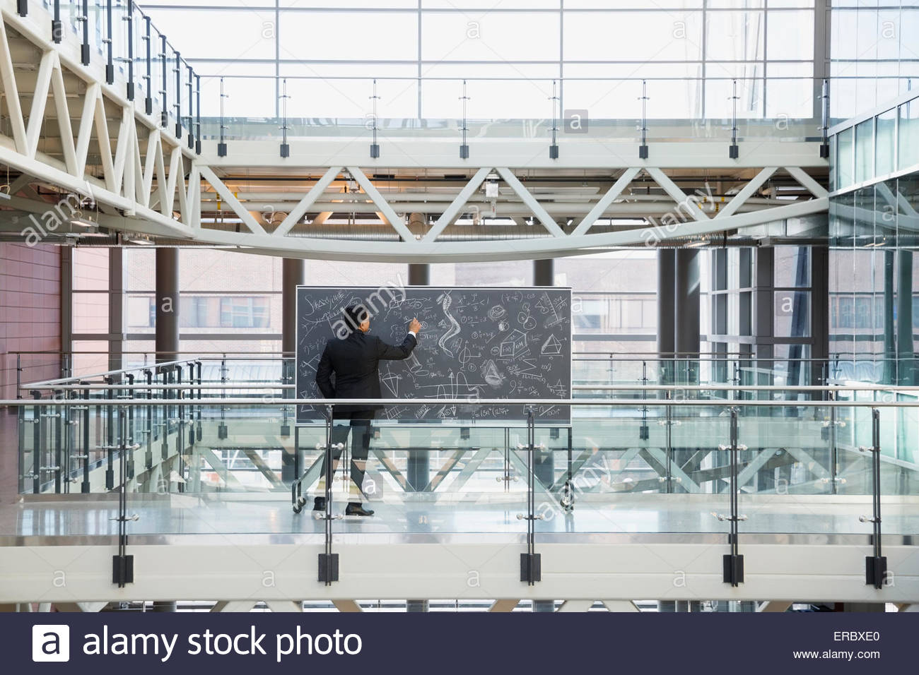 Businessman at blackboard with équations complexes dans l'atrium Photo Stock