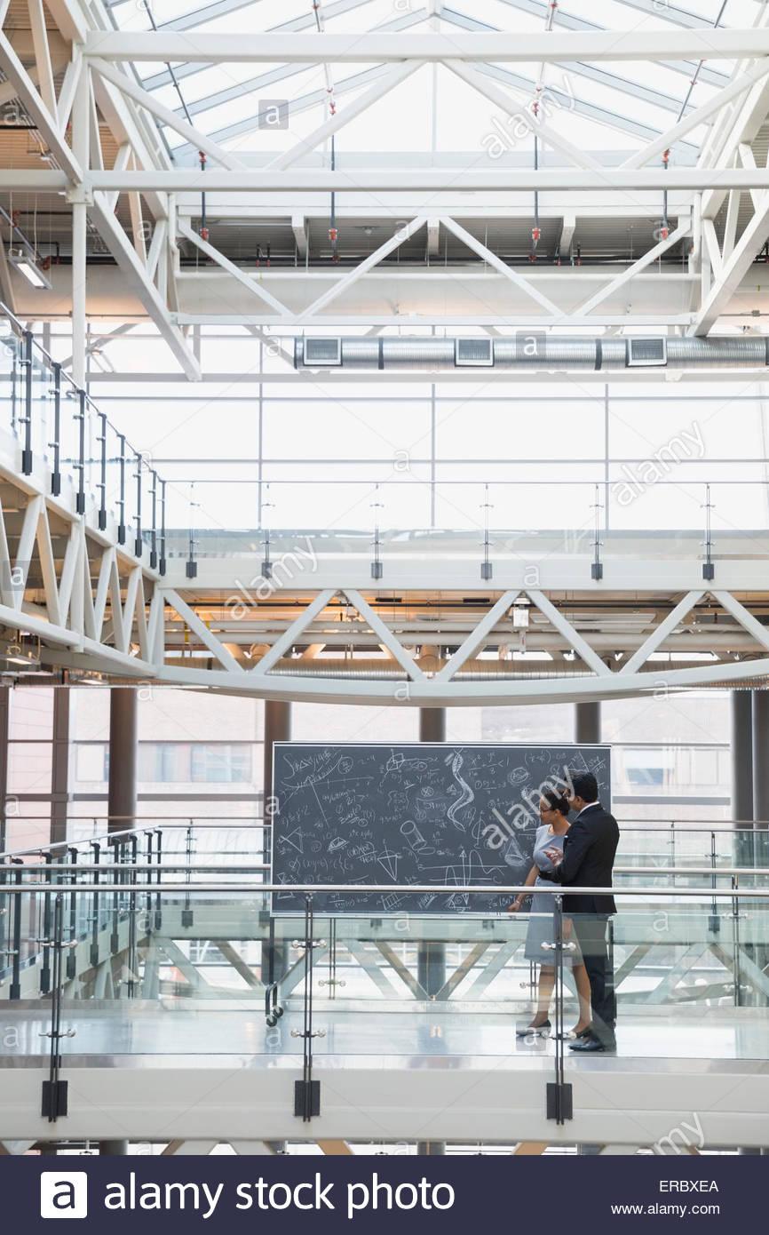 Les gens d'affaires au tableau noir avec des équations complexes atrium Photo Stock