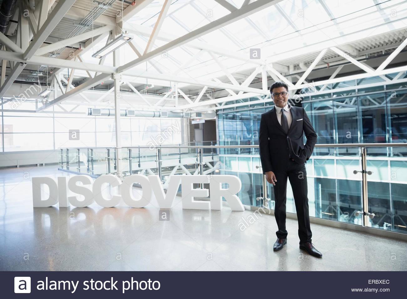 Confident businessman portrait à côté de 'Discover' atrium texte Photo Stock