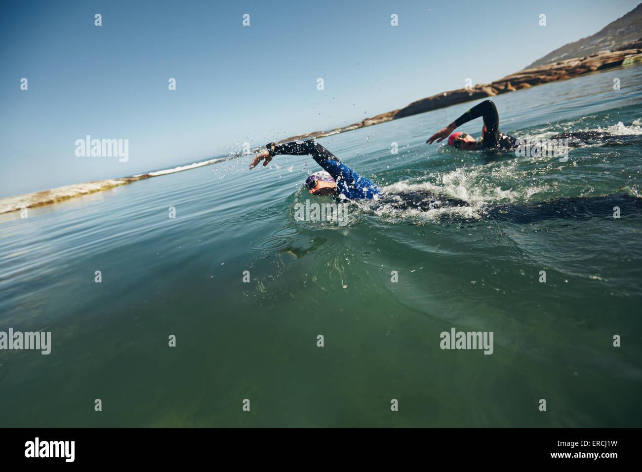 Les athlètes natation sur triathletic la concurrence. Concurrents nage libre dans l'eau. Photo Stock