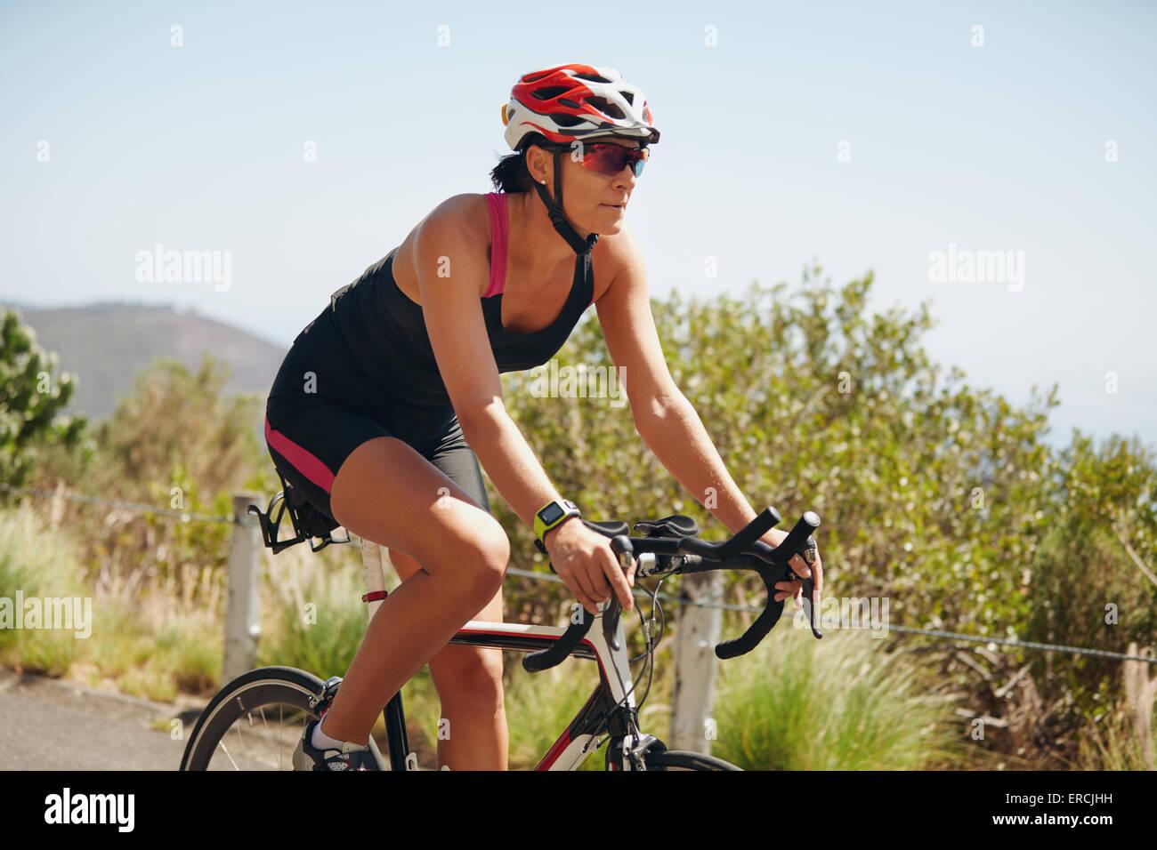 Jeune femme athlète de triathlon vélo sur route de campagne. Woman riding bicycle pour pratiquer la compétition Photo Stock