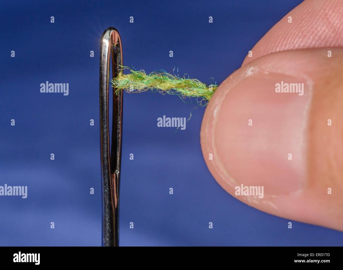 Gros plan de l'aiguille enfilage.les doigts d'un homme enfiler dans le chas d'une aiguille de reprisage. Photo Stock