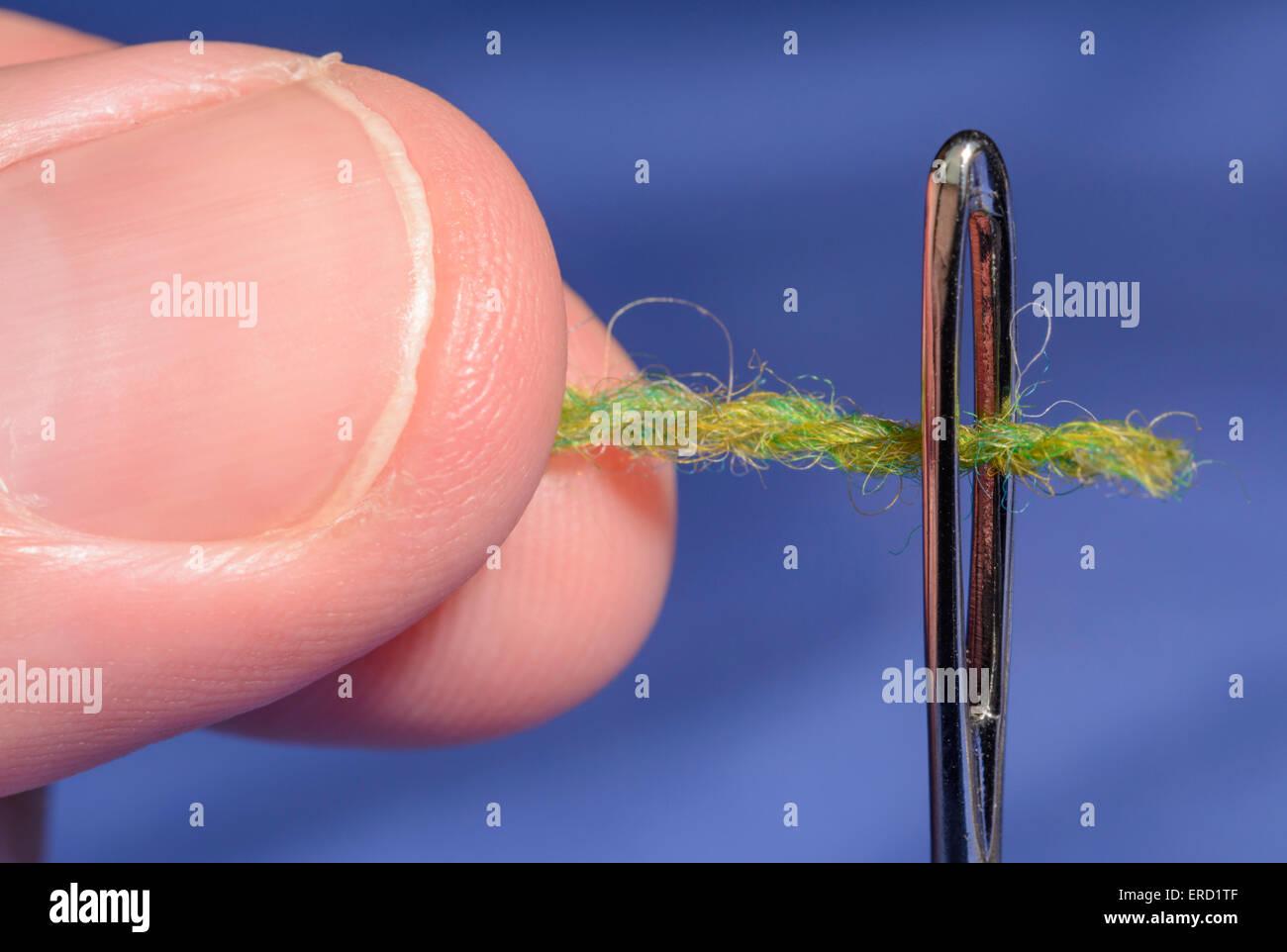 Enfiler une aiguille. L'homme libre de doigts le passage par le trou d'une aiguille de reprisage. Photo Stock