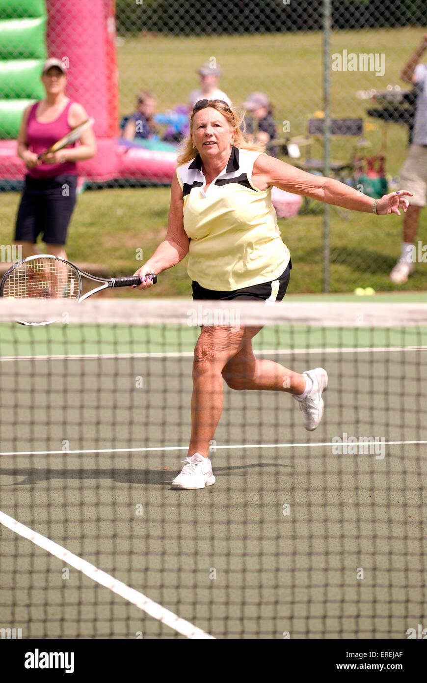 Femme âgée prenant part à un événement de tennis de bienfaisance, Headley, Hampshire, Royaume Photo Stock