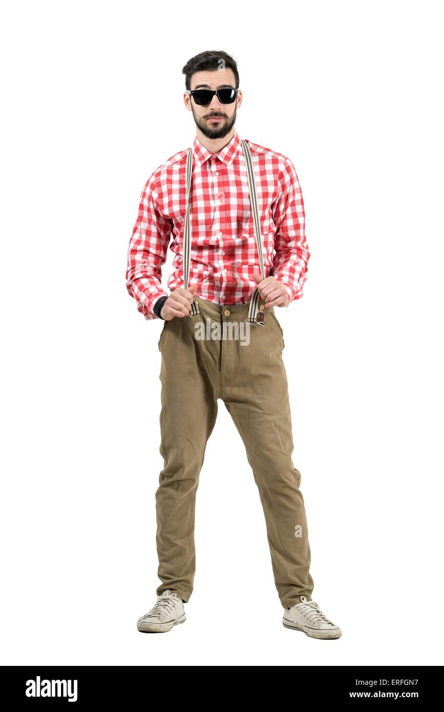 Jeune hipster excentrique qui s'étend des bretelles looking at camera. La longueur du corps complet isolé sur fond Banque D'Images