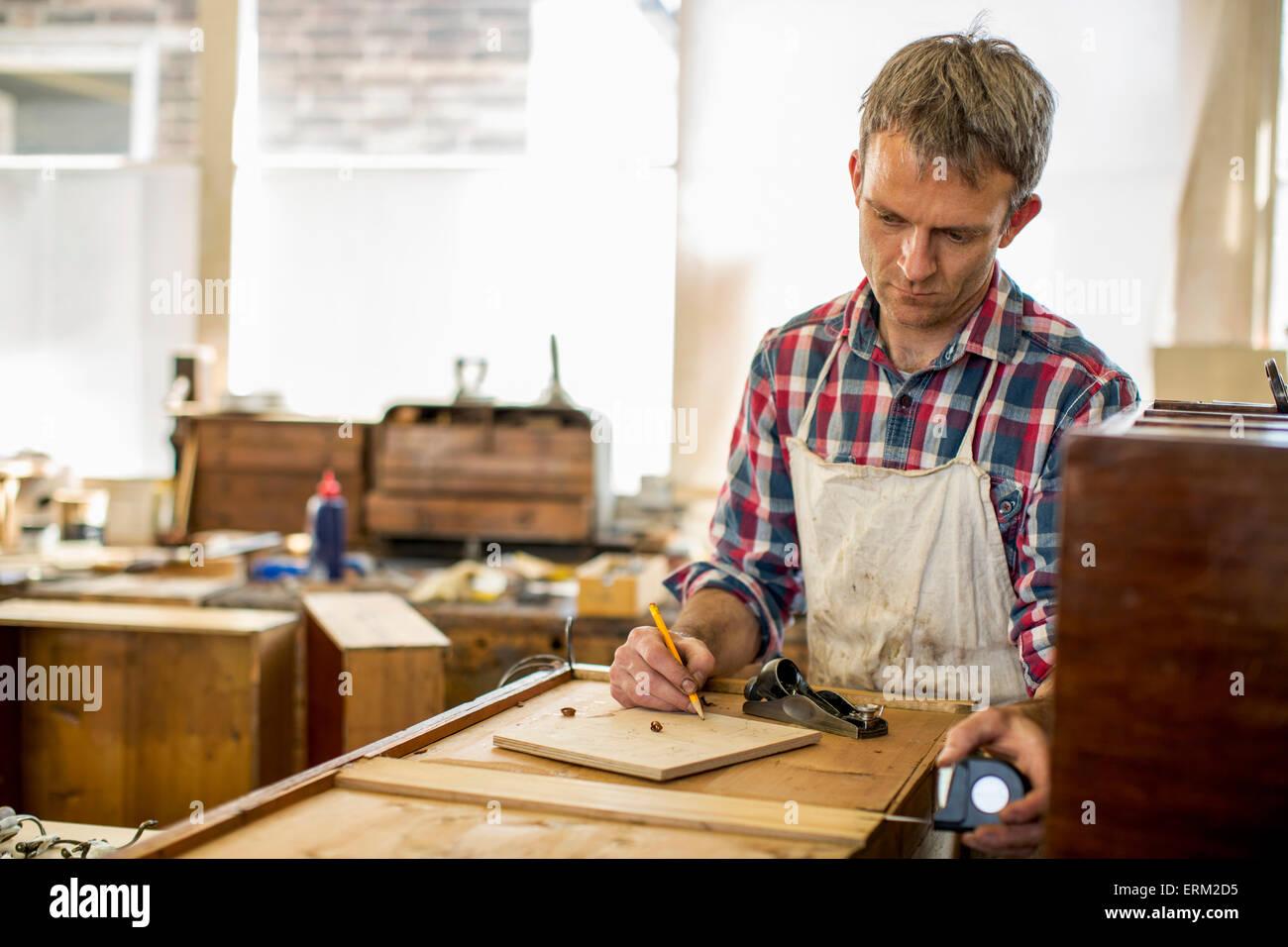 Restaurateur de meubles anciens à l'aide d'un dessin au crayon et à la planification de son travail. Banque D'Images