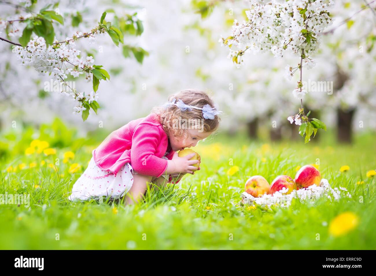 Heureux adorable bébé fille avec des cheveux bouclés et couronne de fleurs portant une robe rouge Photo Stock