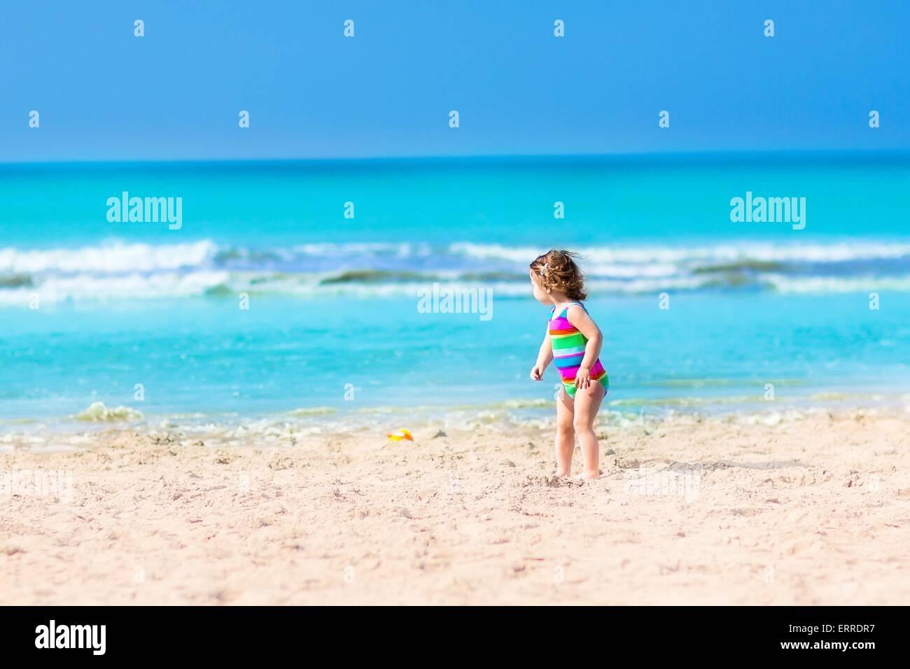 Adorable bébé fille dans un costume de bain coloré jouant sur une belle  plage ensoleillée avec des vagues ee2a3e439af