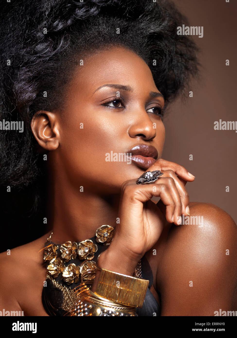 Belle jeune femme africaine avec de grands cheveux de porter des bijoux, beauté artistique portrait sur fond Photo Stock