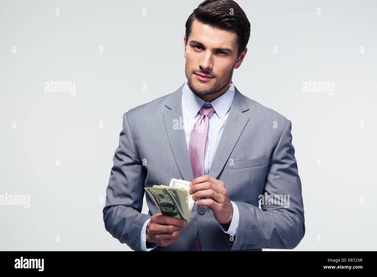 Handsome businessman comptant de dollars sur fond gris et looking at camera Photo Stock