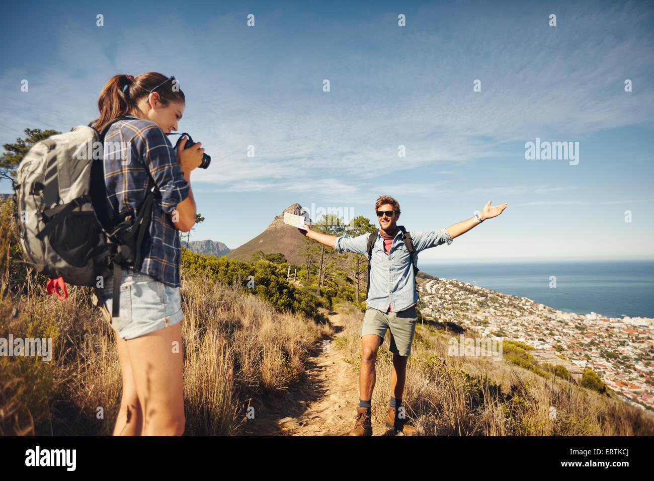 Piscine shot of young woman photographing son petit ami en campagne tout en randonnée. Couple randonneur en Photo Stock