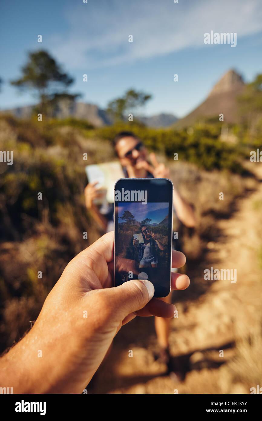 L'homme à prendre des photos sur une jeune femme avec son smartphone. L'accent sur téléphone mobile dans la main. Banque D'Images