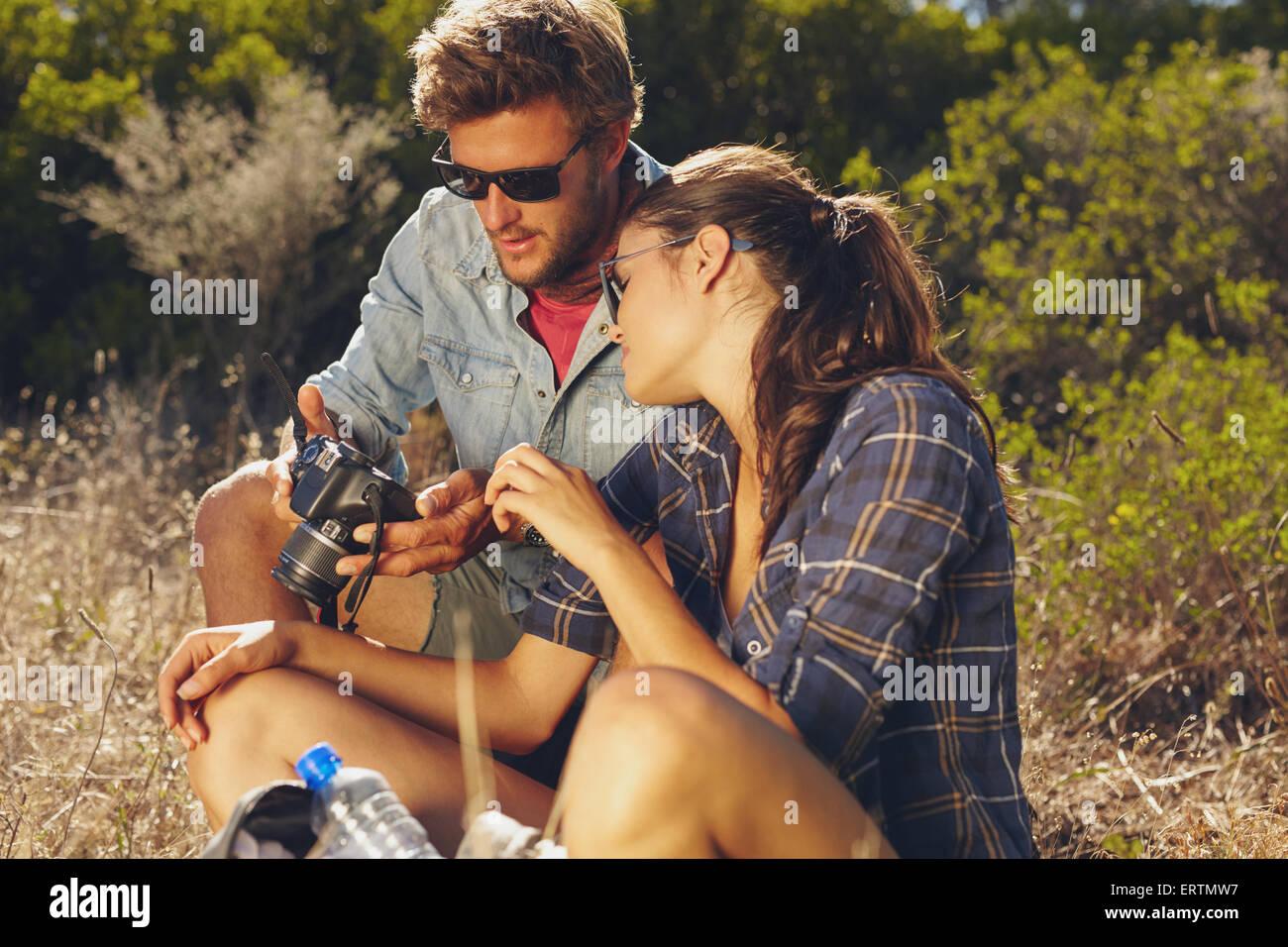 Young couple outdoors ainsi regarder des images sur l'appareil photo numérique. Jeune homme femme sur randonnées Photo Stock