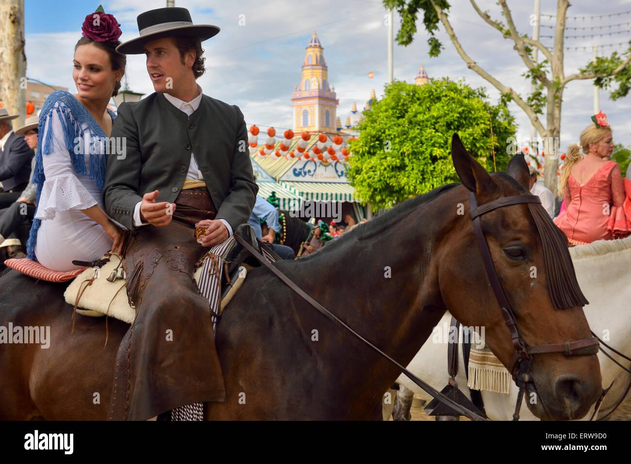 Bel homme et belle femme buvant à cheval avec 2015 entrée principale de la foire d'Avril de Séville Photo Stock
