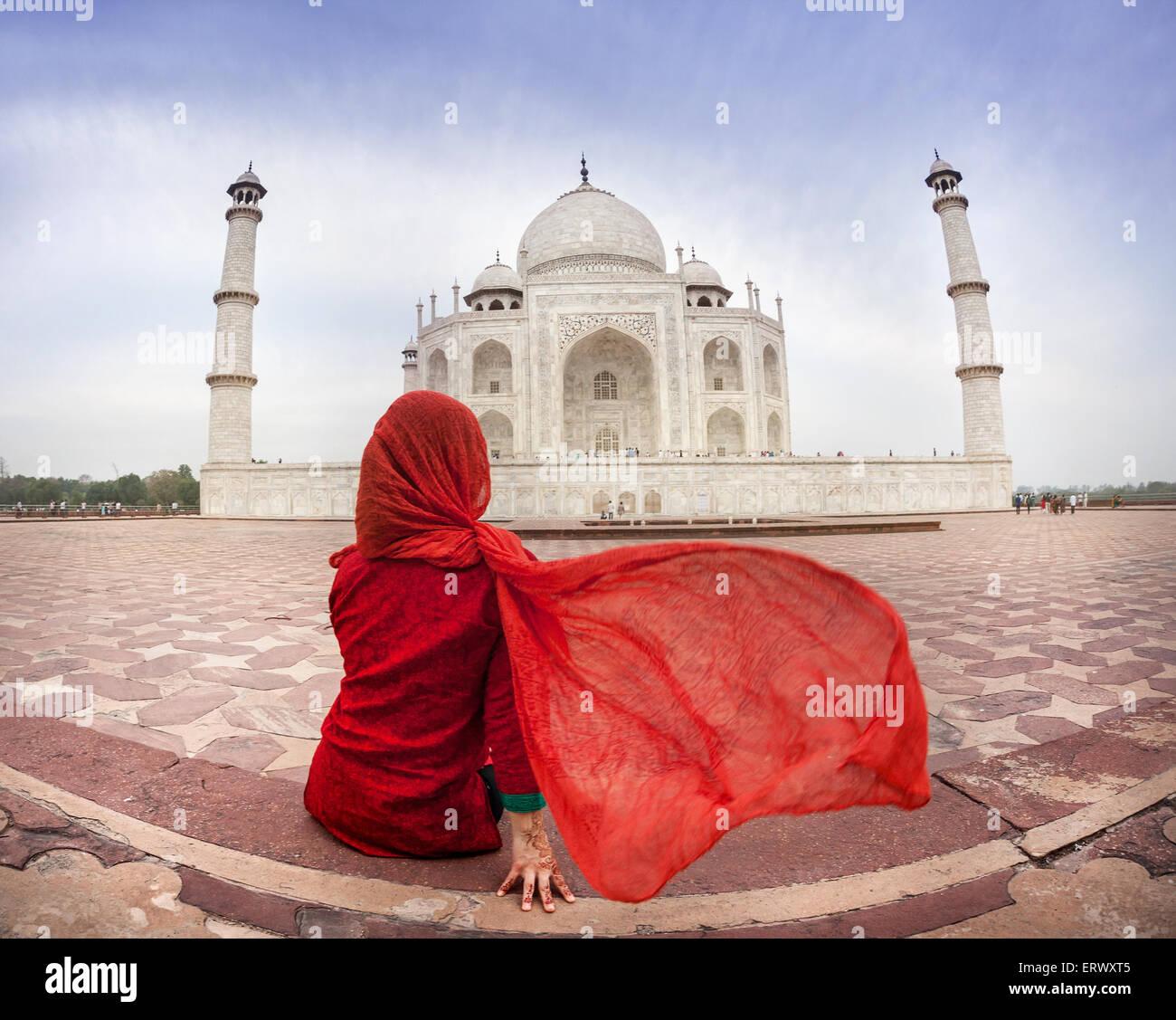 Femme en costume rouge avec écharpe assis près de Taj Mahal à Agra, Uttar Pradesh, Inde Photo Stock