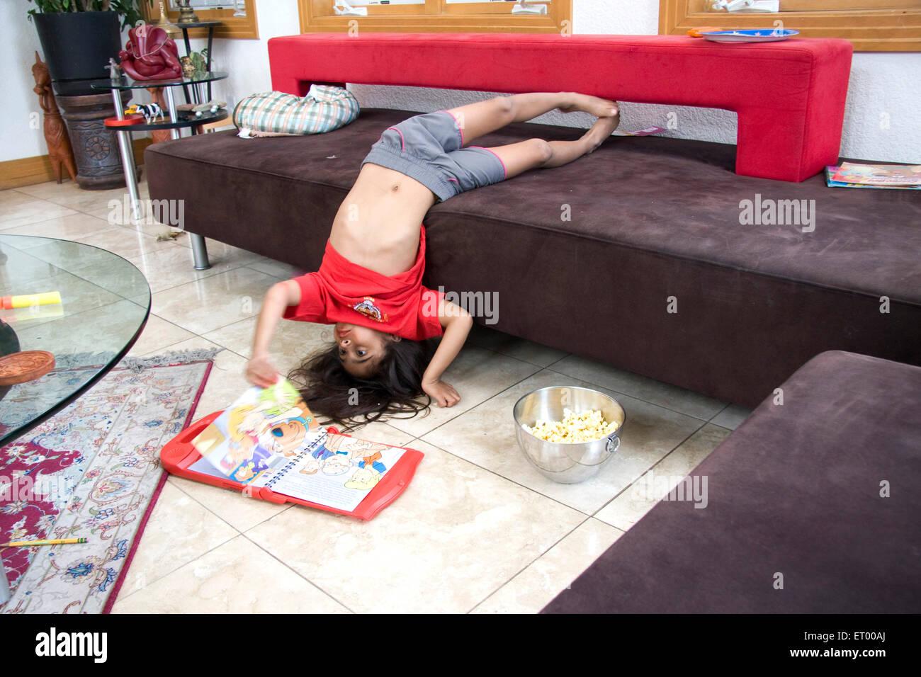 Activité de petite fille de cinq ans qui pose la tête en bas en tournant la page du livre M.#543 Photo Stock