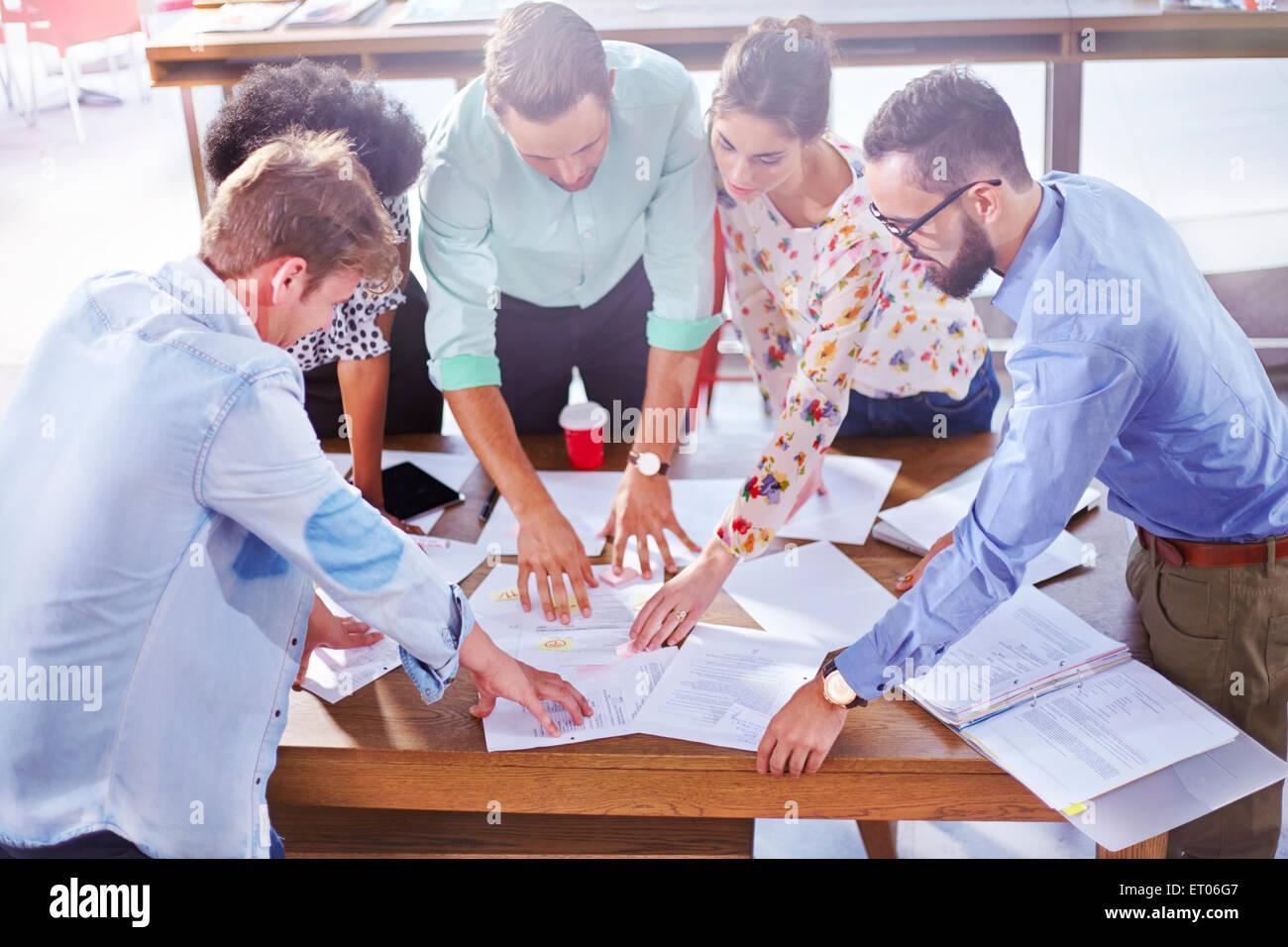 Les gens d'affaires de l'examen en séance de remue-méninges et de la paperasserie Photo Stock