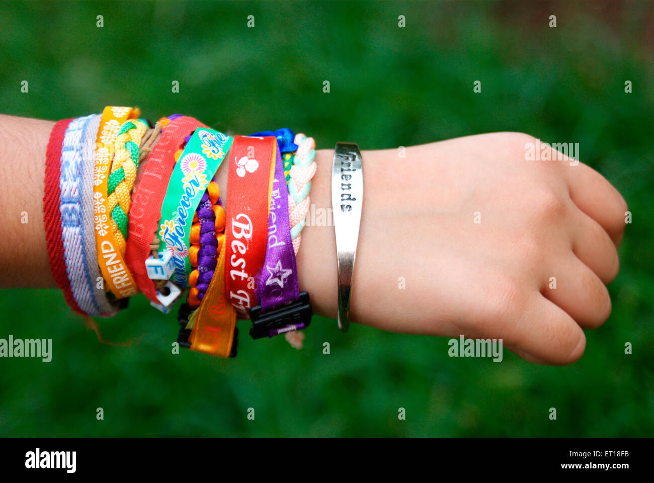 Les bandes de l'amitié bracelets attachés sur fond vert à la main - M.#364 - Photo Stock