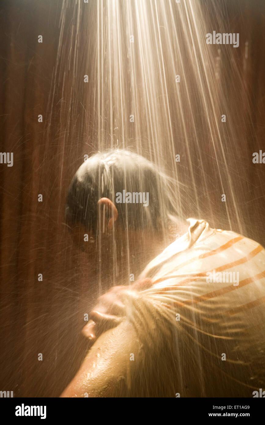 Echelle de l'homme sous l'eau de douche salle de bains dans le bain de lumière; plage de Palolem Photo Stock