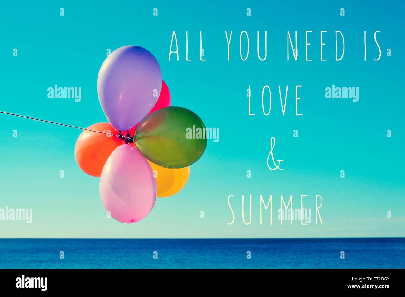 Un bouquet de ballons de différentes couleurs sur le fond bleu du ciel avec la mer en arrière-plan et le texte tout ce qu'il vous faut, c'est l'amour un Banque D'Images