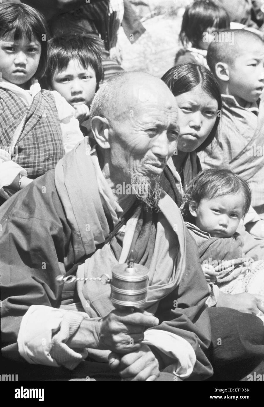 Vieil homme habillé en costume traditionnel fait tourner la roue de prière au festival; Bhoutan Banque D'Images