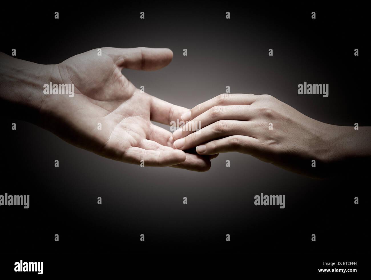 Deux mains se touchent sur fond noir, notion de solidarité ou de l'empathie. Photo Stock