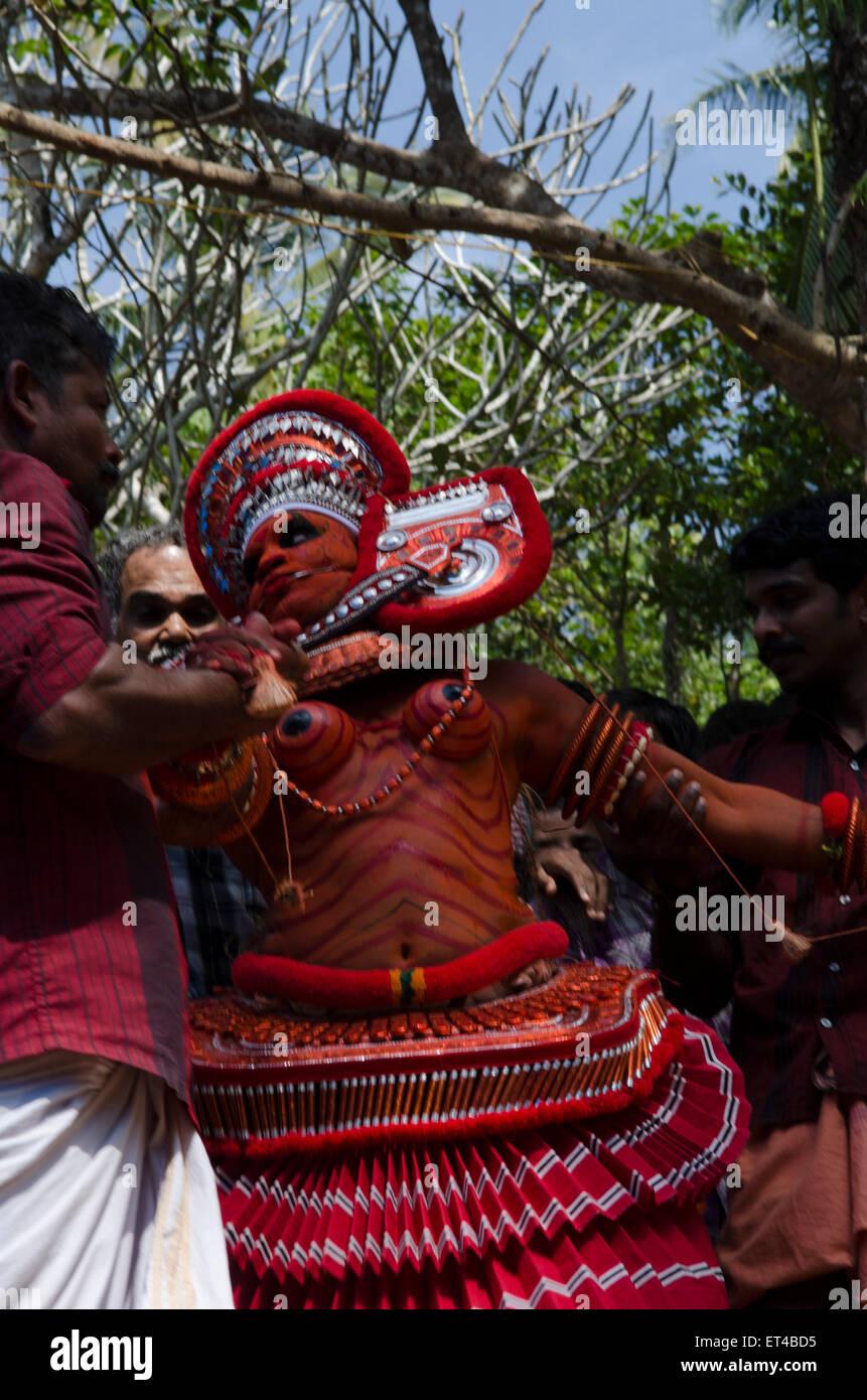 Un danseur theyyam est poussé et tiré à travers l'arène dans le cadre de l'ancienne Photo Stock
