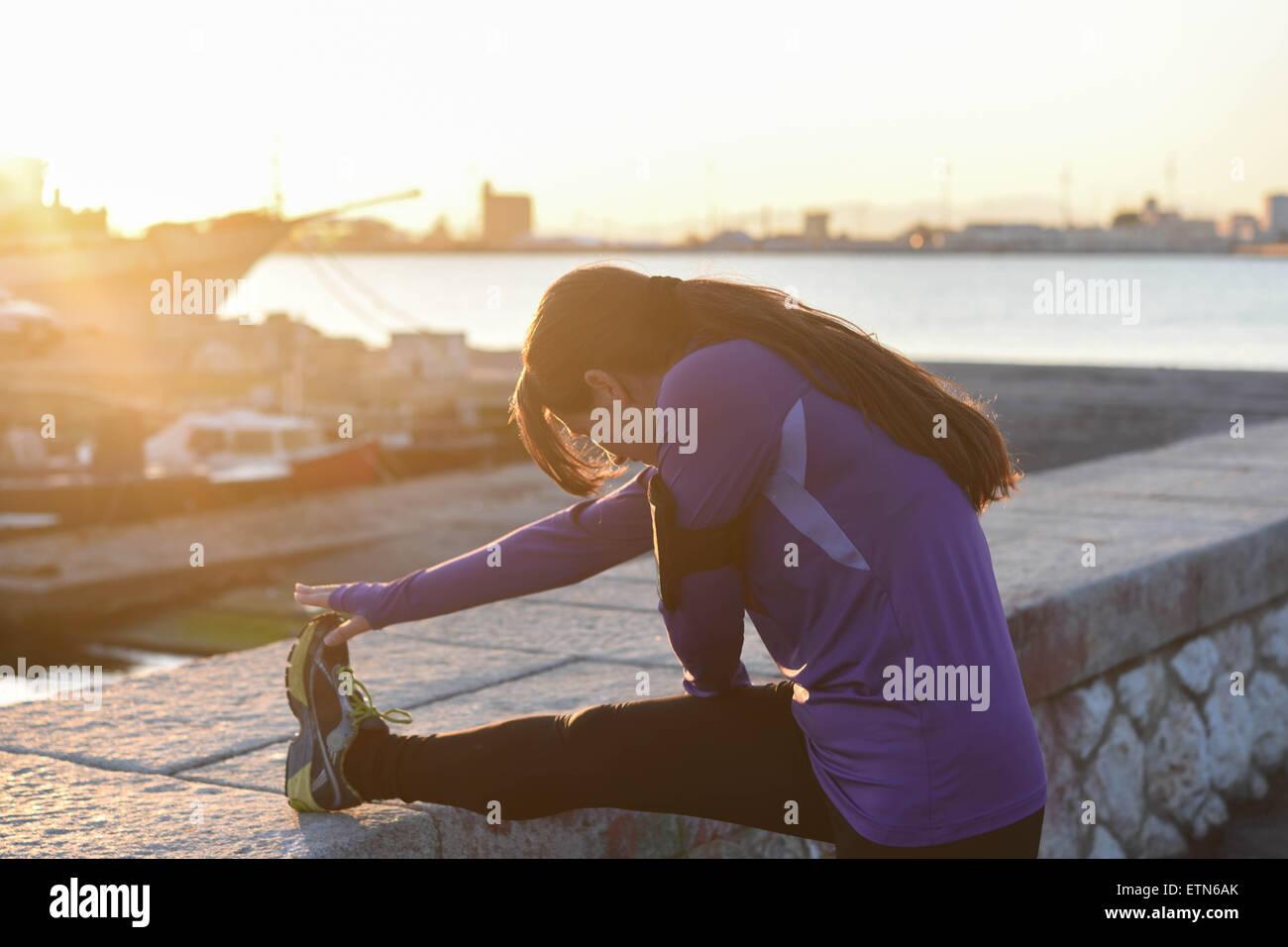 Jeune femme étend sa jambe sur un mur au coucher du soleil Photo Stock