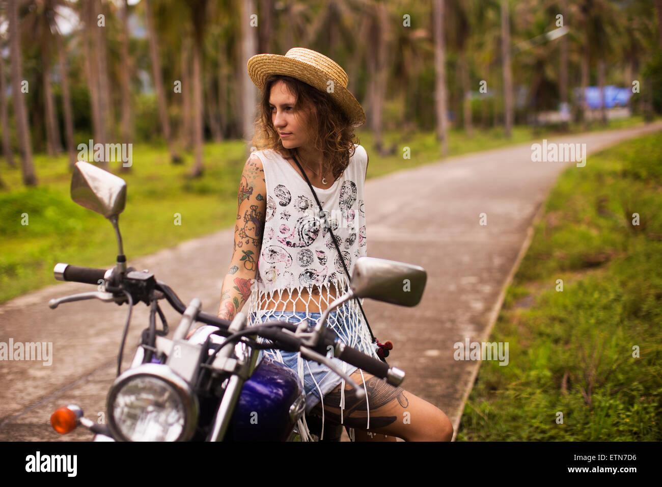 Edgy femme tatouée assis sur une moto Photo Stock