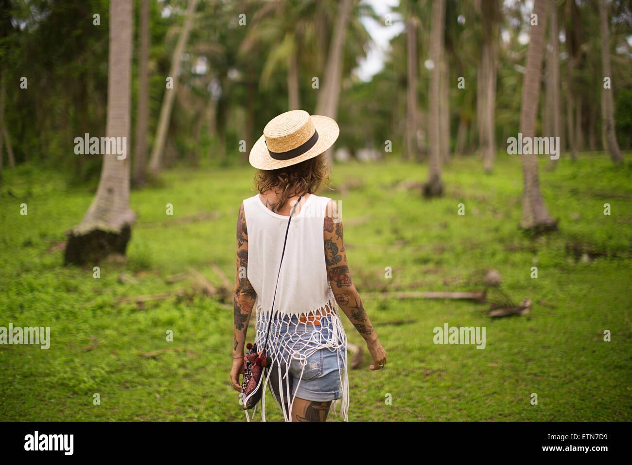 Vue arrière d'une femme marchant dans un jardin tropical, la Thaïlande Photo Stock