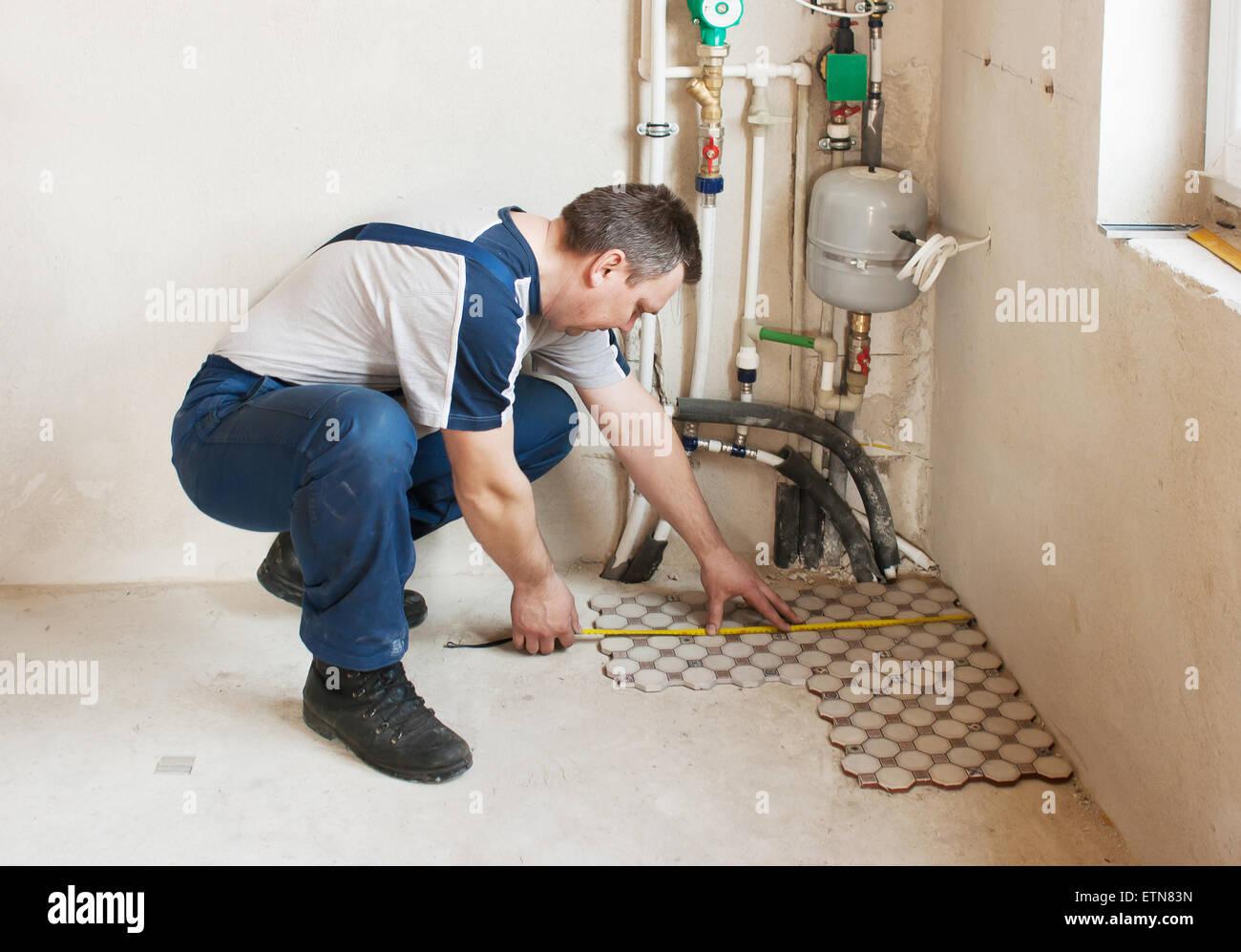 Carreaux de sol pose l'homme dans une nouvelle maison Photo Stock