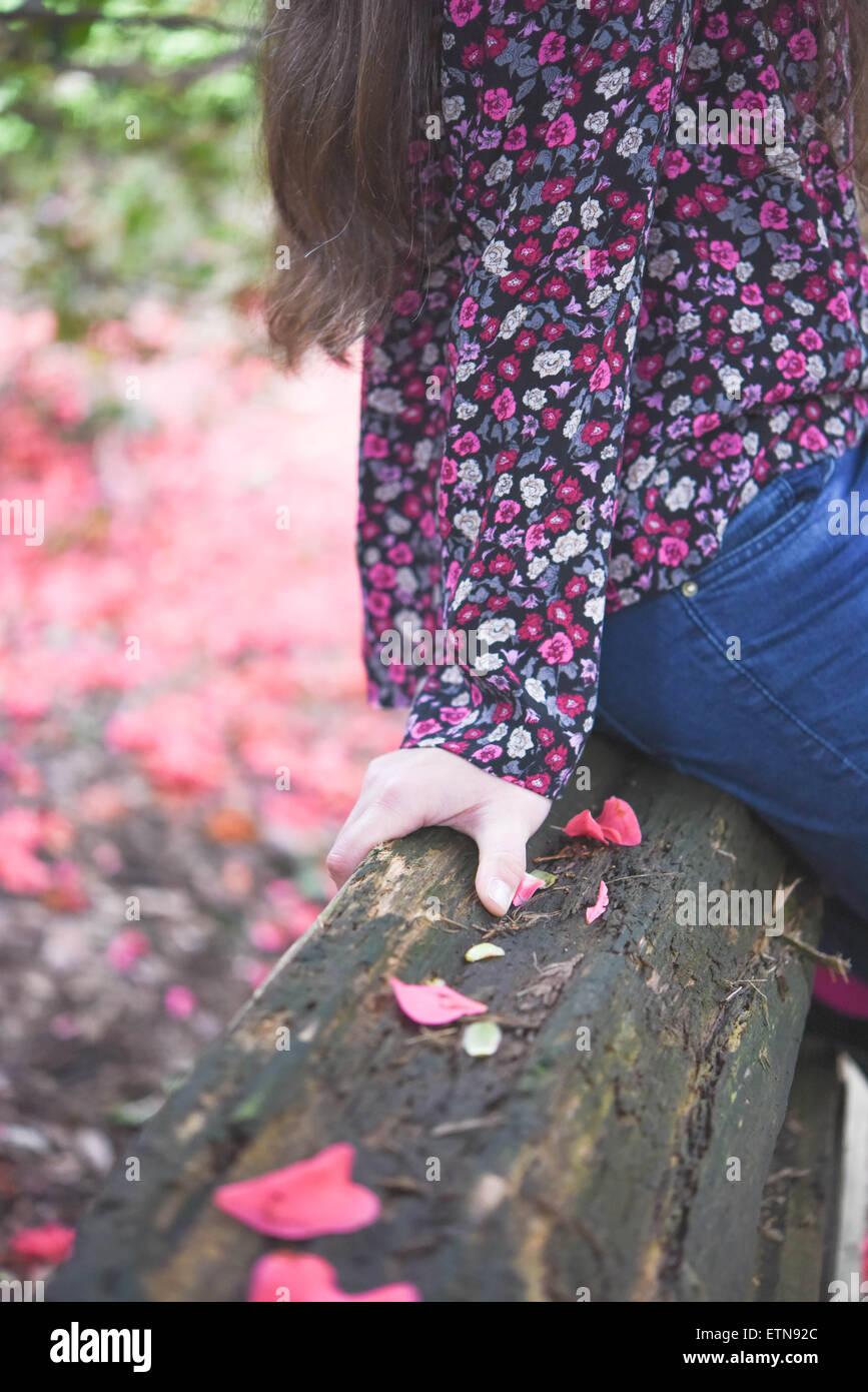 Close-up d'une partie d'une femme assise sur une clôture en bois, Vancouver, Canada Photo Stock