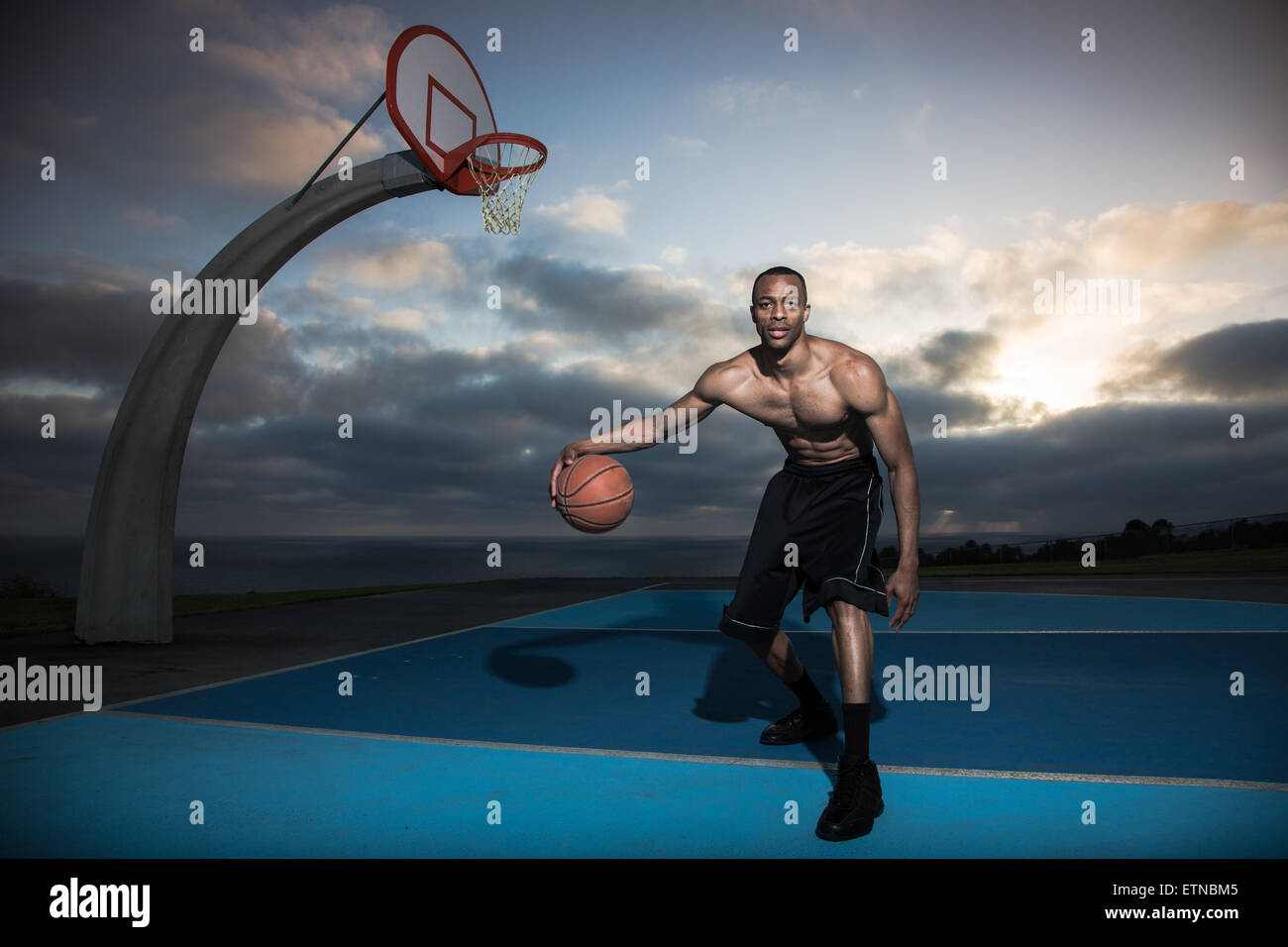 Jeune homme jouant au basket-ball dans un parc, Los Angeles, Californie, USA Photo Stock
