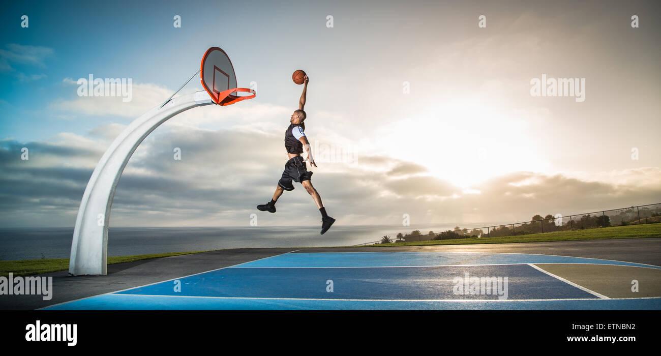 Jeune homme jouant au basket-ball dans un parc, Los Angeles, Californie, USA Photo Stock