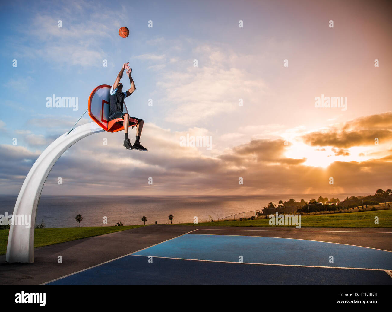 Jeune homme assis dans un panier de basket-ball dans un parc, Los Angeles, Californie, USA Photo Stock