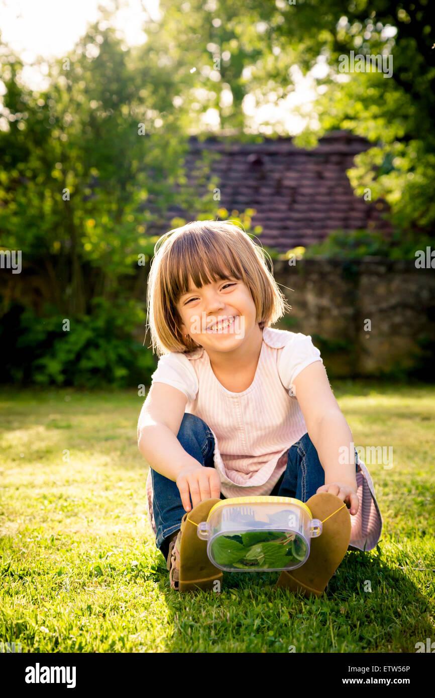 Petite fille avec insecte peut assis sur un pré Banque D'Images