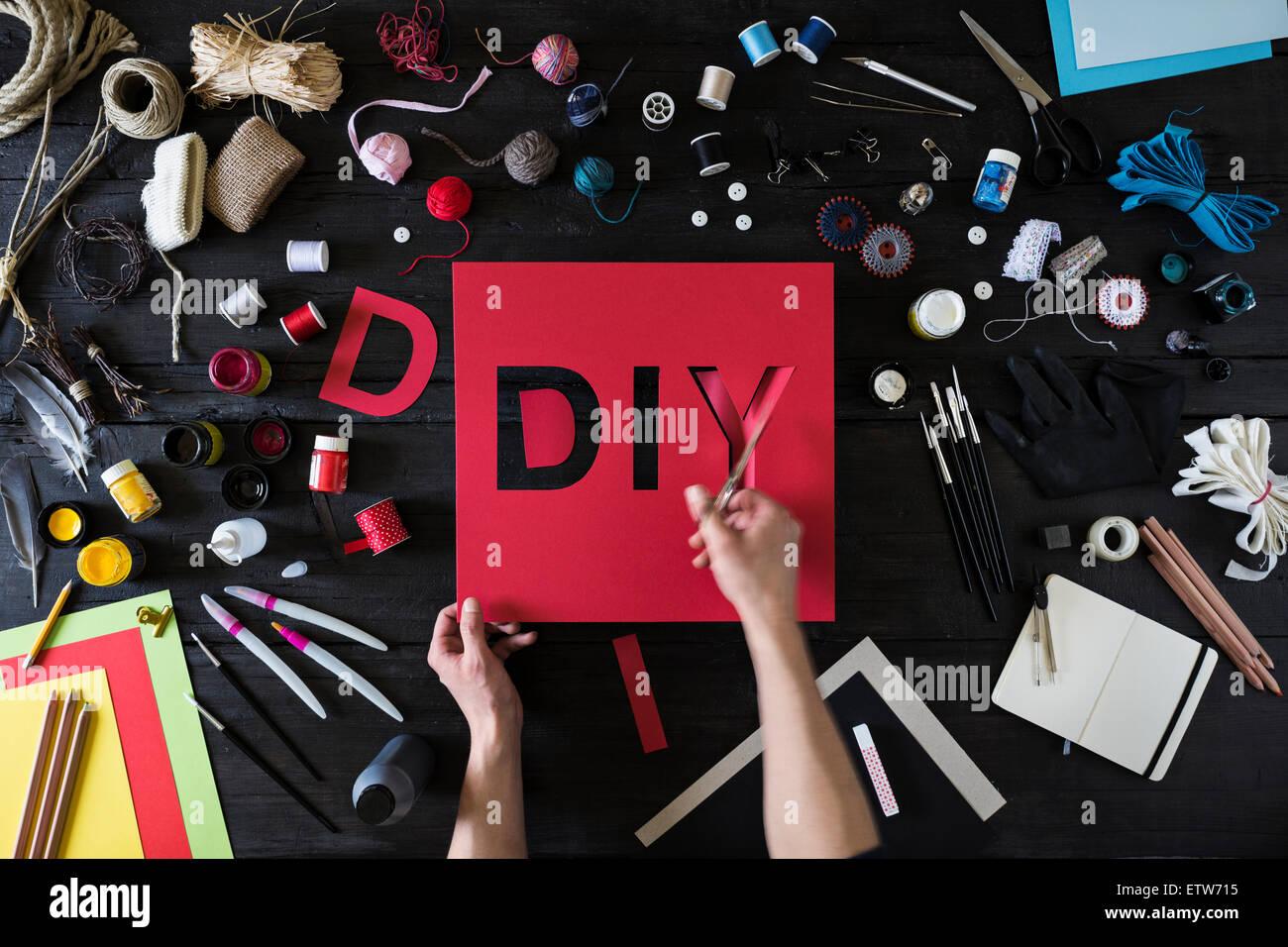 Les mains de l'homme coupe la parole de bricolage carton rouge Photo Stock