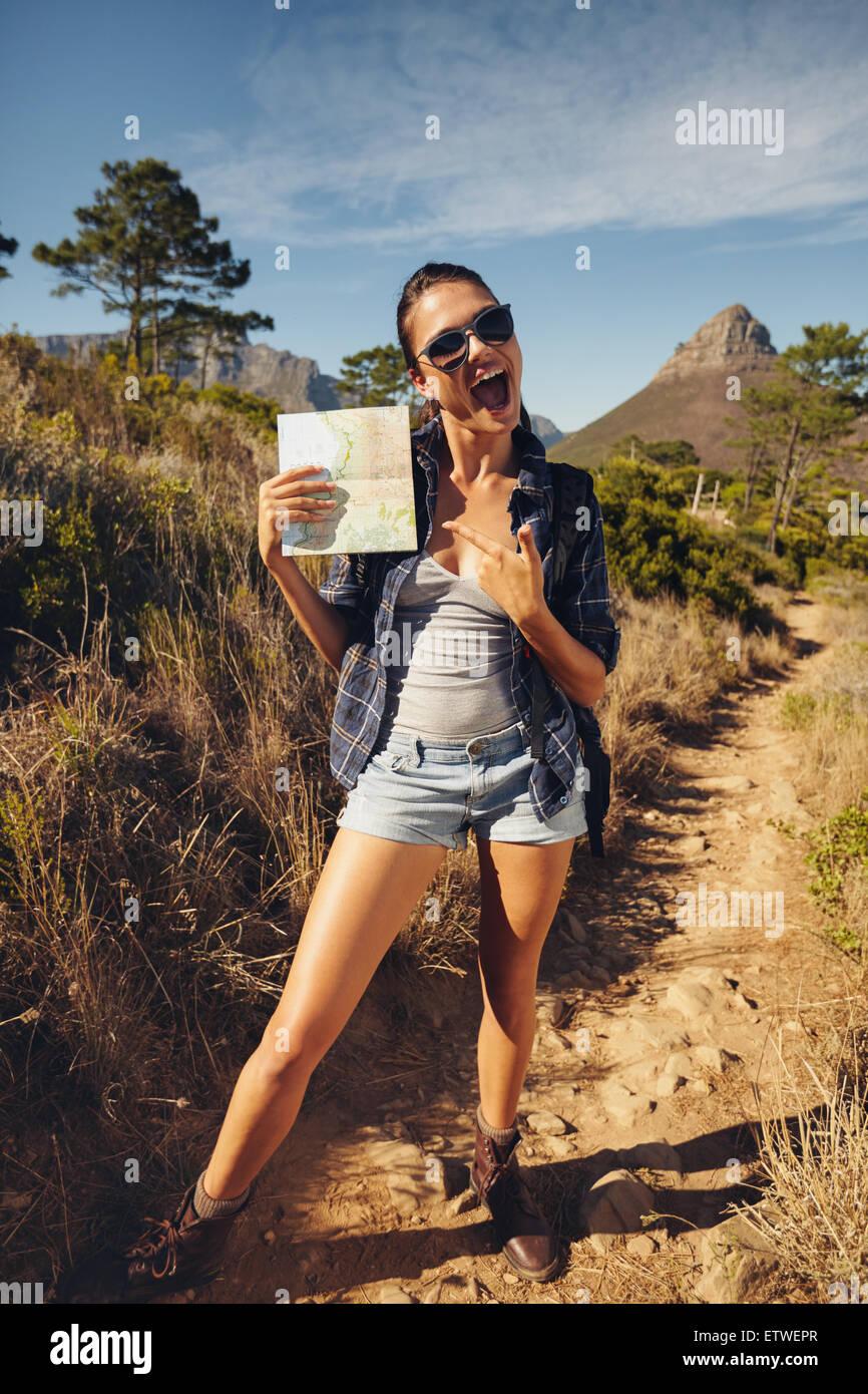 Portrait de jeune femme hiker montrant une carte. Caucasian woman hiking in countryside sur journée d'été. Photo Stock