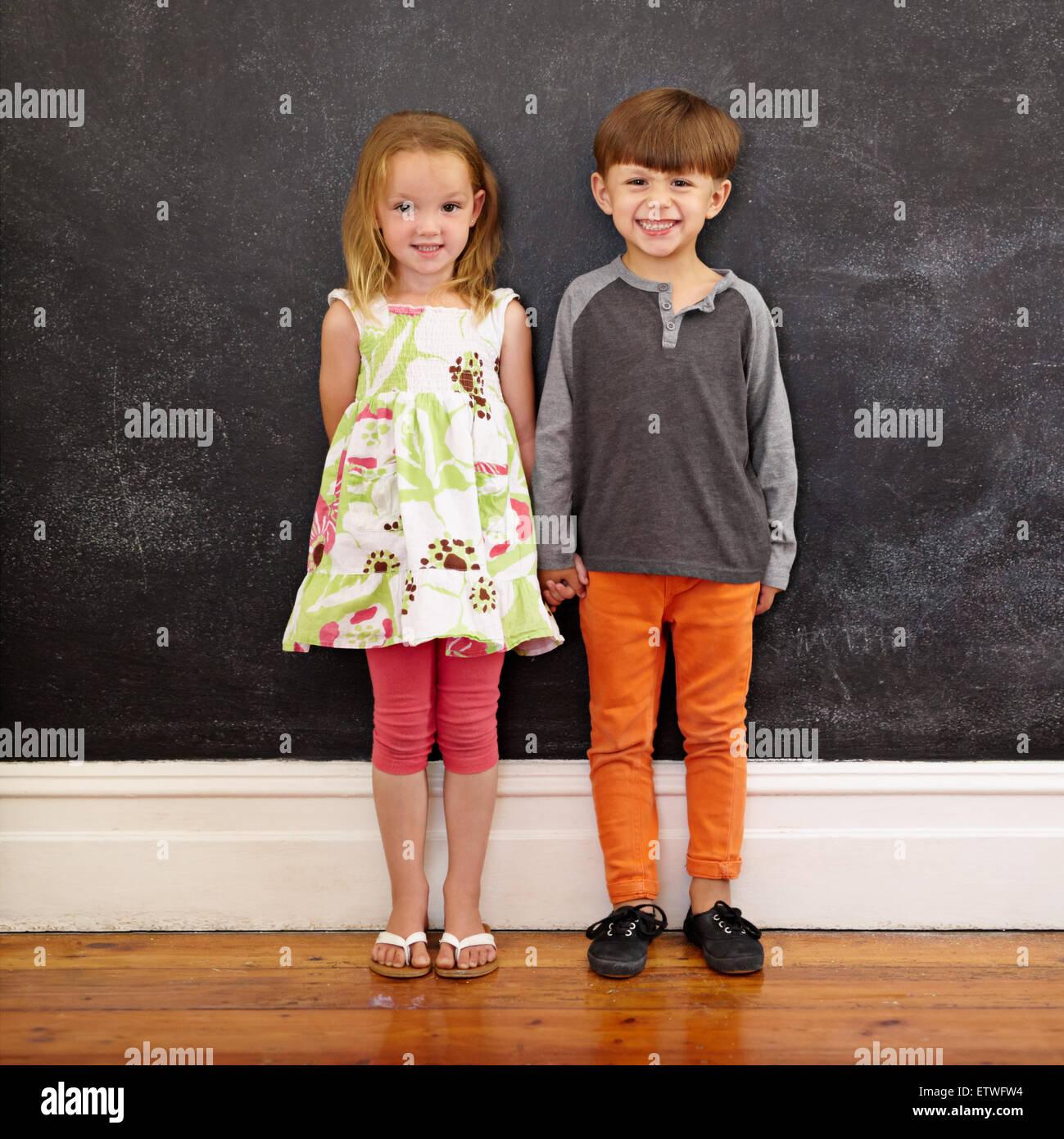 toute la longueur de balle deux jeunes enfants se tenant ensemble contre un tableau noir petit. Black Bedroom Furniture Sets. Home Design Ideas