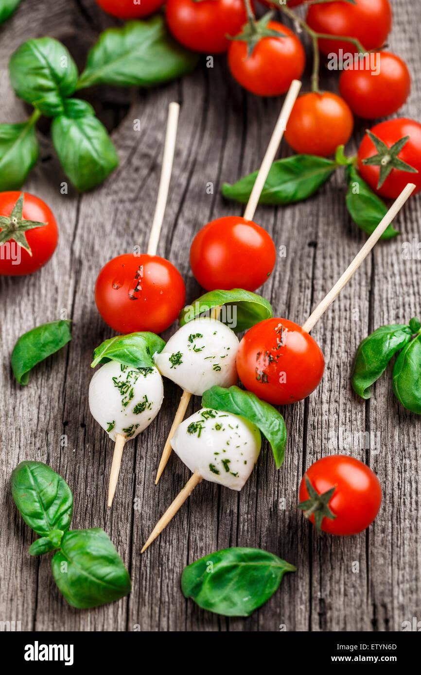 Brochettes avec tomate, basilic et mozzarella sur un fond rustique Photo Stock