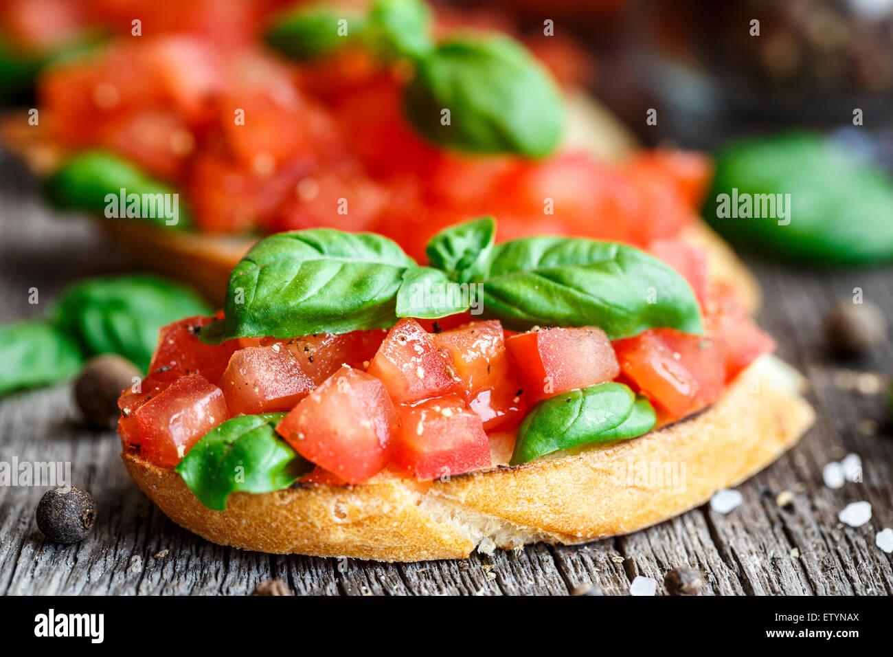 Bruschetta aux tomates et concassé de tomates au basilic sur pain grillé Photo Stock