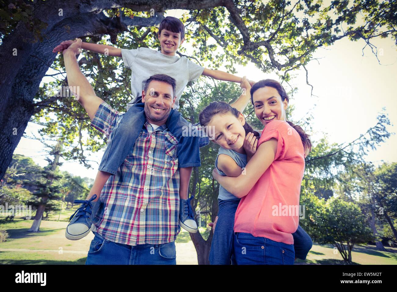 Famille heureuse dans l'ensemble du parc Photo Stock