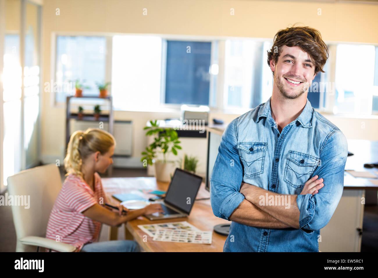 Smiling businessman posing avec son partenaire derrière lui Photo Stock