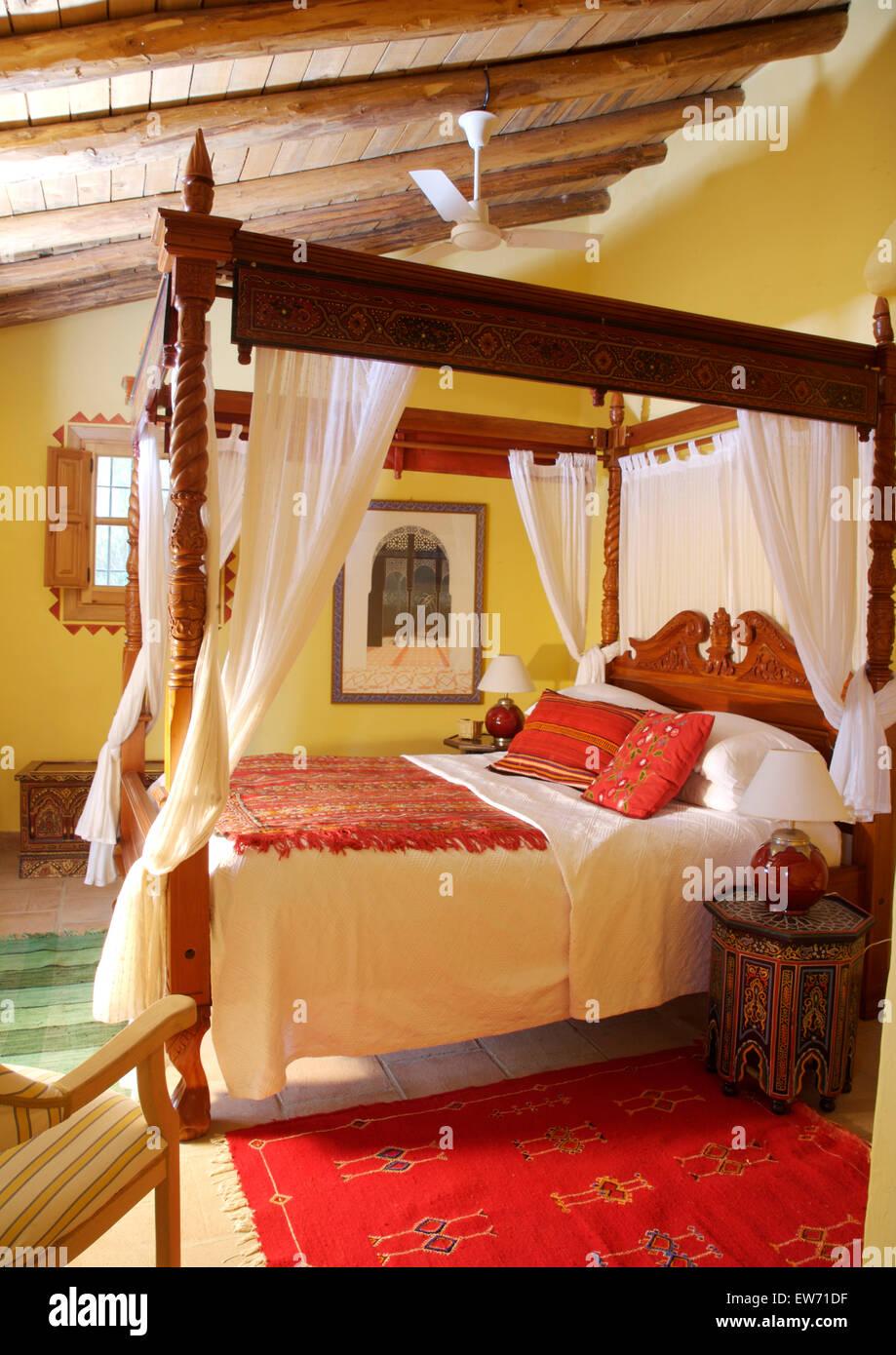 Coussins et tapis rouge ethnique sur lit à baldaquin en bois ...