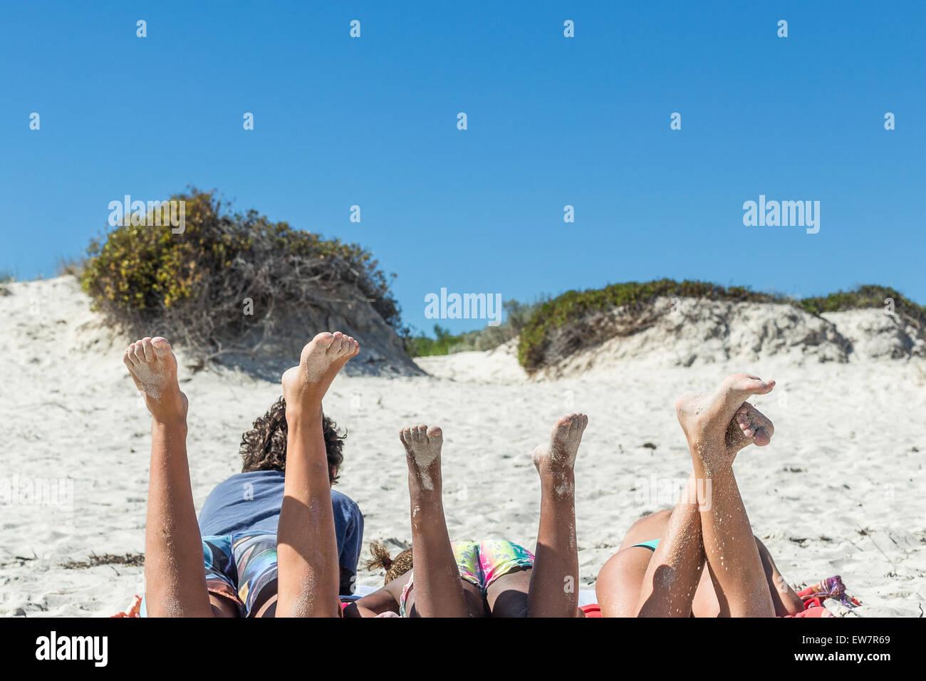 Trois enfants sur la plage avec leurs jambes en l'air Photo Stock