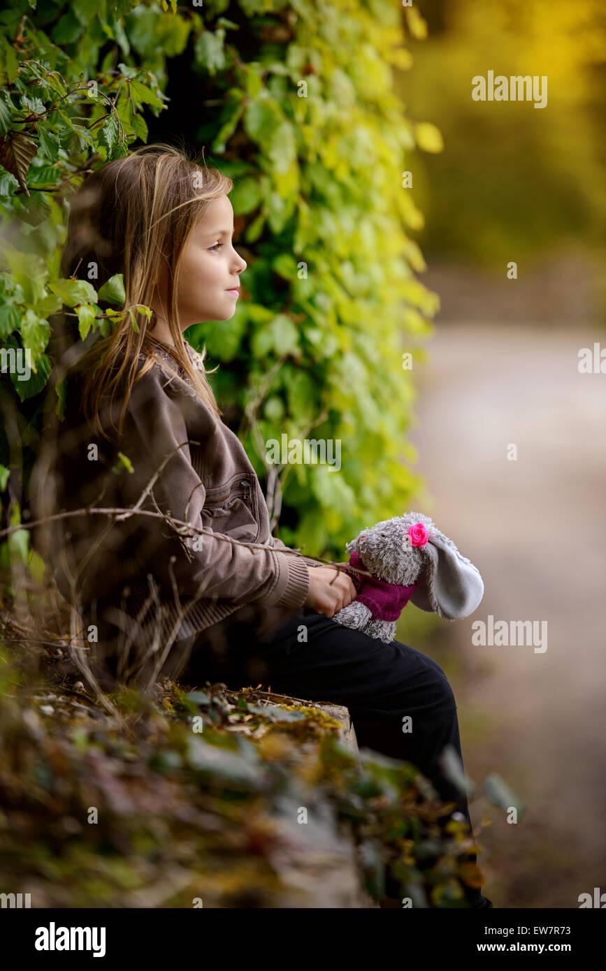 Vue latérale d'une jeune fille tenant un lapin en peluche jouet Photo Stock