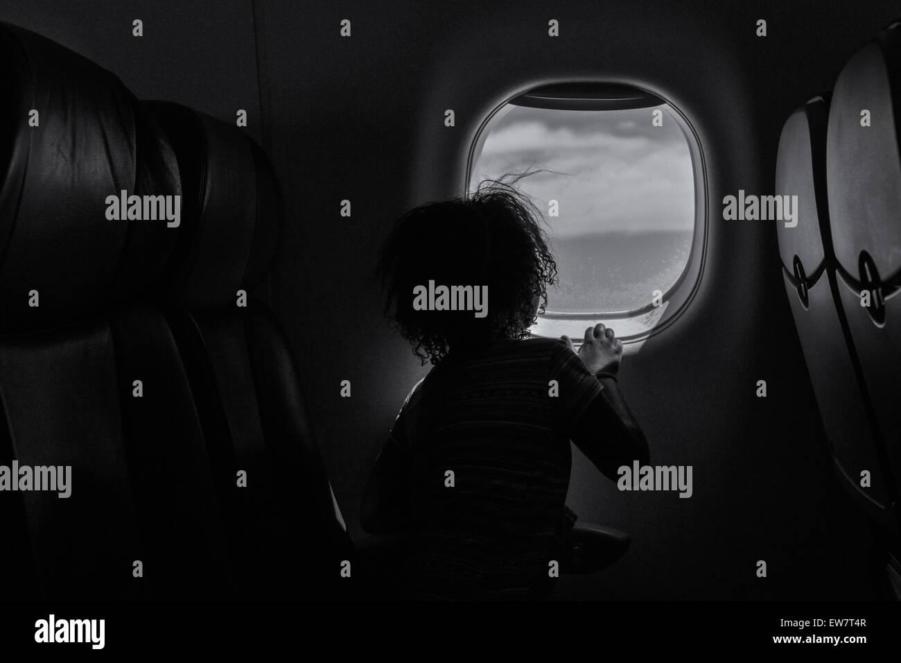 Vue arrière d'une jeune fille regardant par la fenêtre dans un avion Photo Stock