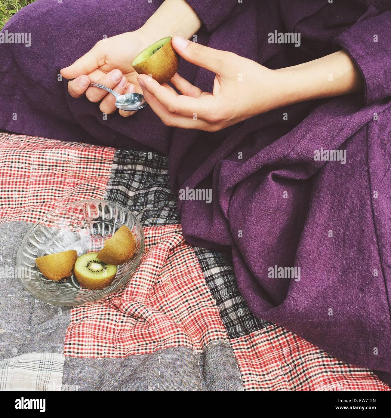 Close-up of a woman eating kiwi Photo Stock